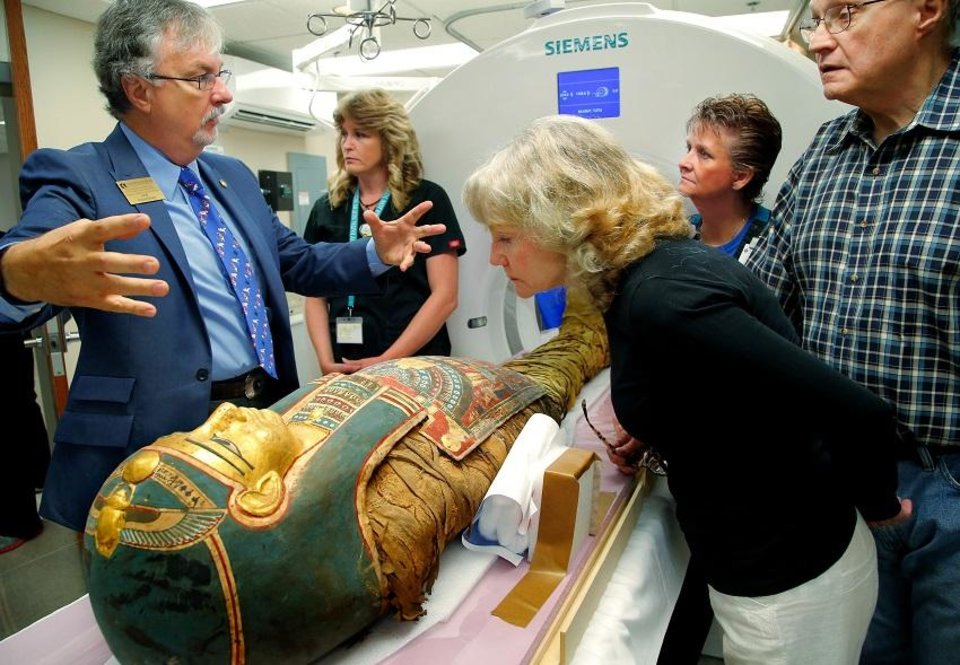 Photo - Robert Pickering, left, an anthropologist with the University of Tulsa, talks about the Mabee-Gerrer Museum of Art mummy known as Tutu as it is readied to be placed into the scanner on Thursday morning, Aug, 20, 2015. Leaning down is Megan Clement, chairwoman of the board of directors for the Mabee-Gerrer Museum. Curators from the Mabee-Gerrer Museum crated their two mummies and delivered them in 2015 to SSM Health St. Anthony Shawnee Hospital, where technicians performed CT scans. CT, or CAT scans, are special X-ray tests that produce cross-sectional images of the body [Jim Beckel/The Oklahoman Archives]