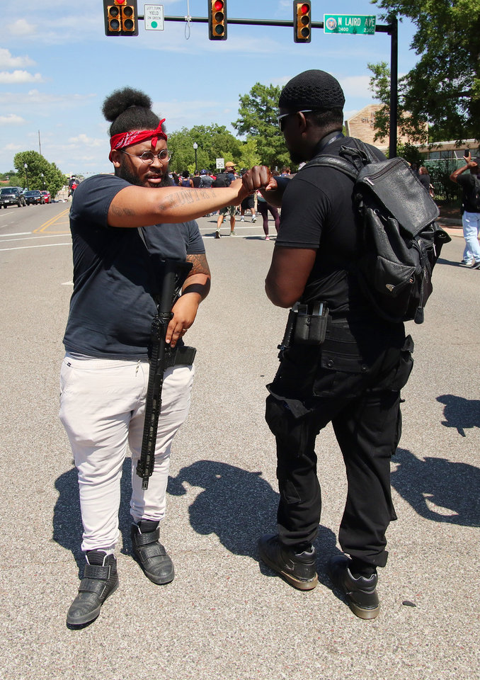 Photo - Omar Chatman gives a fist bump to a participant at a 1,000 brothers and sisters in arms for second amendment walk by predominantly black men and women to advocate for their second amendment rights, Saturday, June 20, 2020. [Doug Hoke/The Oklahoman]