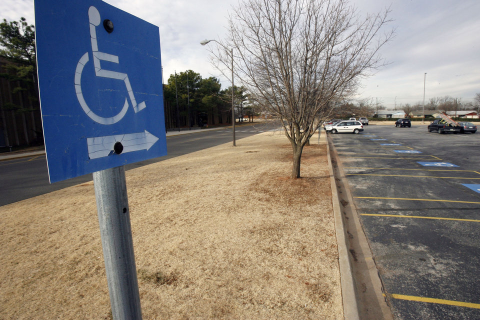 Photo - The handicapped parking spaces at the Oklahoma Science Museum in Oklahoma City, OK, are marked with signs with arrows. Friday, Jan. 23, 2009. BY PAUL HELLSTERN, THE OKLAHOMAN ORG XMIT: KOD