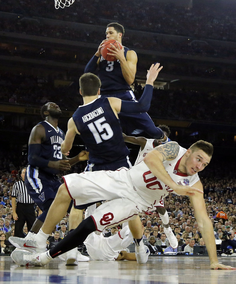 Photo - Villanova's Josh Hart (3) grabs a rebound next to teammates Daniel Ochefu (23) and Ryan Arcidiacono (15) as Oklahoma's Ryan Spangler (00) falls to the court in the send half during the national semifinal between the Oklahoma Sooners (OU) and the Villanova Wildcats in the Final Four of the NCAA Men's Basketball Championship at NRG Stadium in Houston, Saturday, April 2, 2016. Photo by Nate Billings, The Oklahoman