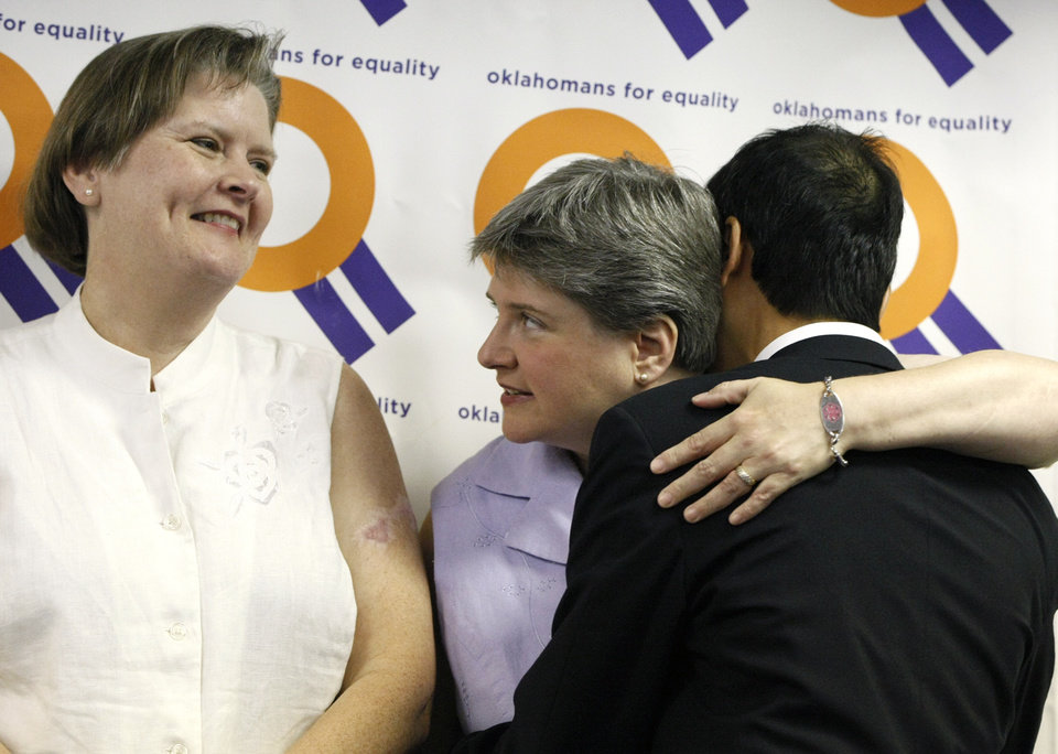 Photo - Sharon Baldwin (center) hugs attorney Joe Thai (right) while standing with her partner Mary Bishop (left) after a press conference at the Dennis R. Neill Equality Center in Tulsa, Okla. on Monday, October 6, 2014. MATT BARNARD/Tulsa World