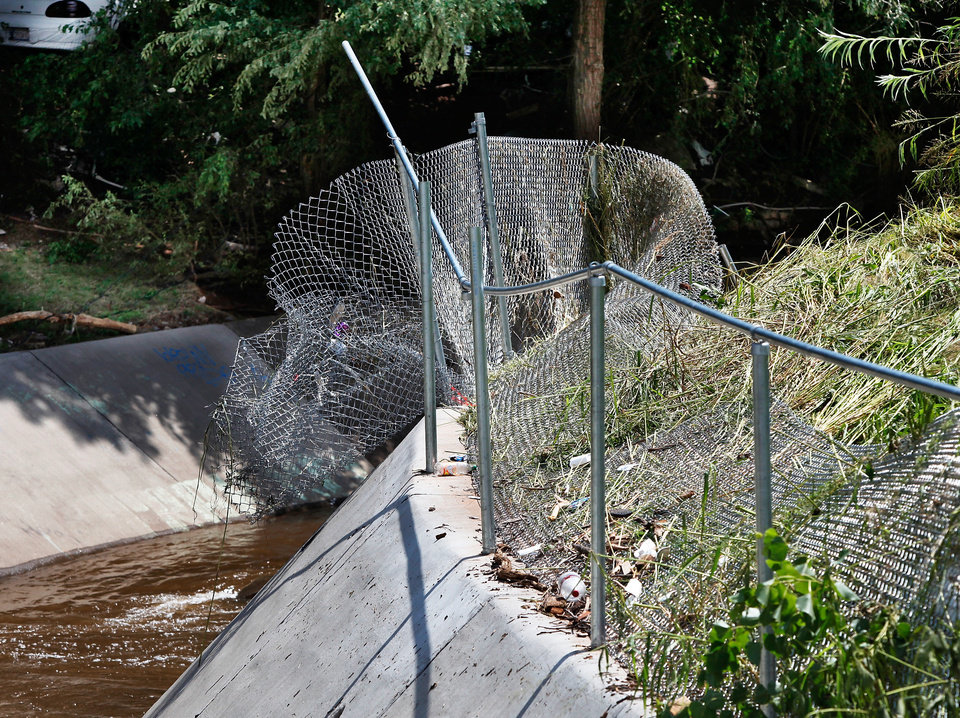 Photo - Mangled fencing behind a home on the west bank of Lightning Creek near SW 27 and Broadway. Raging flood water destroyed large sections of the chain link fence last night. Residents cleaned homes and yards in the area near Lightning Creek in south Oklahoma City, Friday, July 9, 2010. Heavy rains last night caused the  creek to overflow its banks, flooding the areas on both sides of the creek.  Staff Photo by Jim Beckel , The Oklahoman