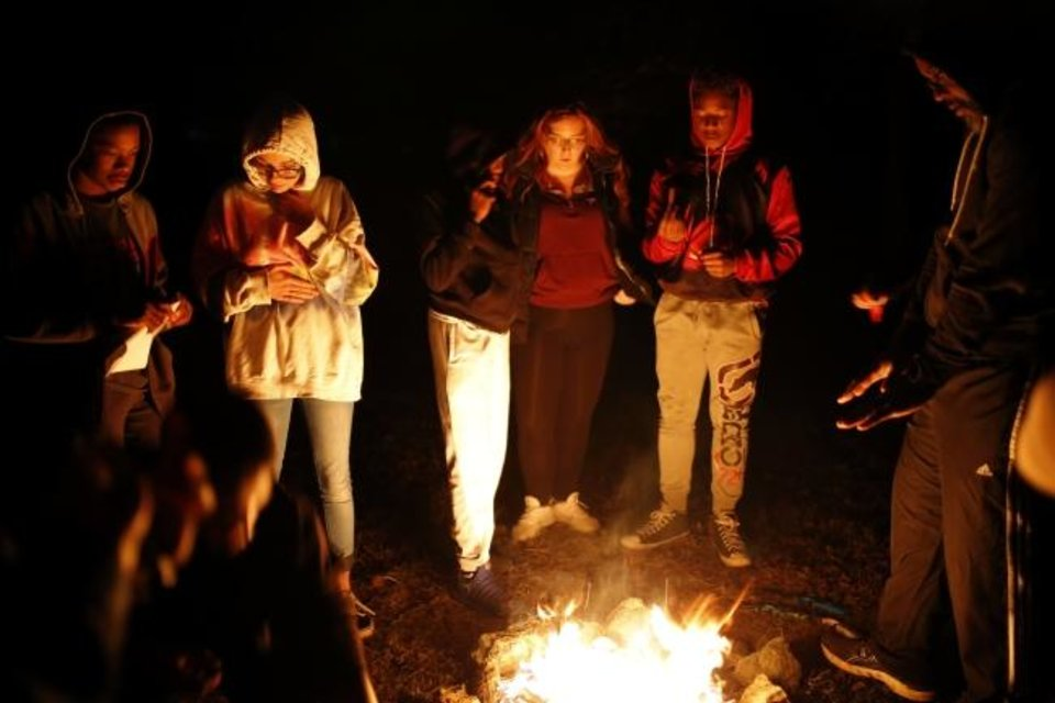 Photo -  Youth and mentors gather around a fire during a recent outdoors class in Yukon. [Sarah Phipps/The Oklahoman]