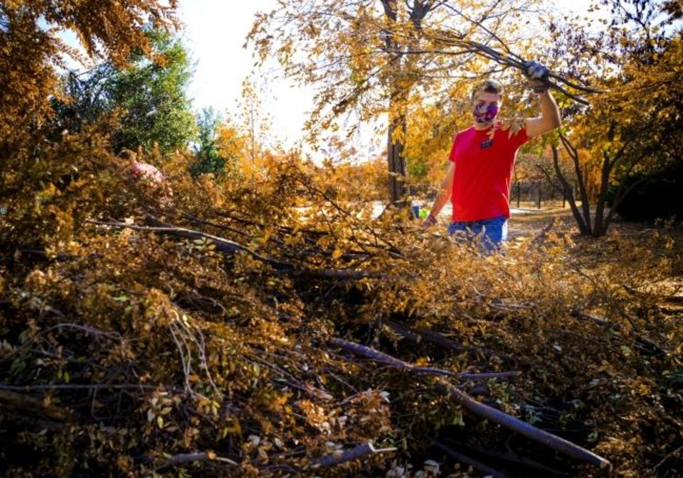 Photo -  Blake Goodsell, a Church of Jesus Christ of Latter-day Saints missionary, helps clean up storm damage on Friday at Perle Mesta Park in Oklahoma City. [Chris Landsberger/The Oklahoman]