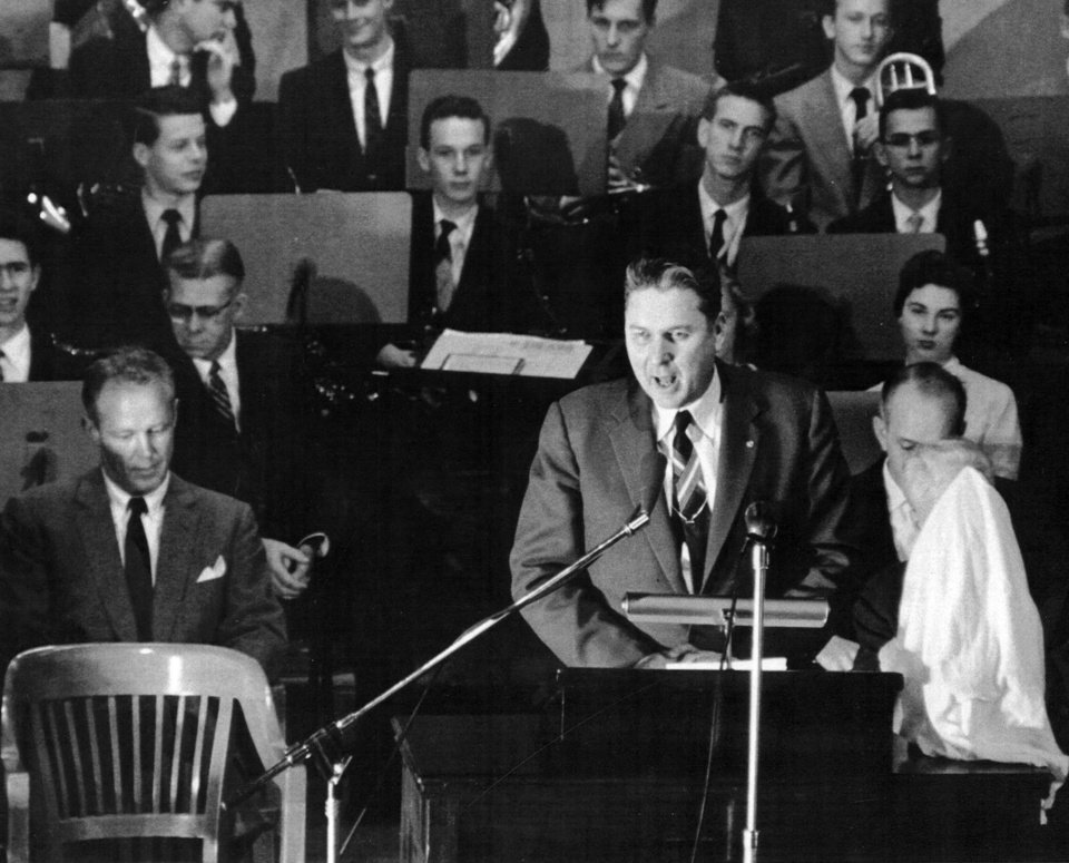 Photo -  Oklahoma Gov. Raymond Gary addresses the Holmberg Hall audience during the ceremony to award the 1956 national football championship award, the Grantland Rice Trophy. At  left is OU head football coach Bud Wilkinson. [Photo Provided by OU]