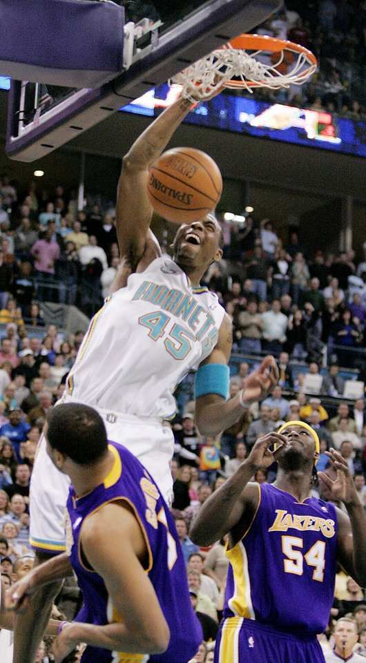 Photo - Rasual Butler of the Hornets dunks over Devean George, left, and Kwame Brown of the Lakers during the New Orleans/Oklahoma City Hornets NBA basketball game against the Los Angeles Lakers at the Ford Center in Oklahoma City, Feb. 4, 2006. The Hornets beat the Lakers 106-90.  By Bryan Terry/The Okahoman