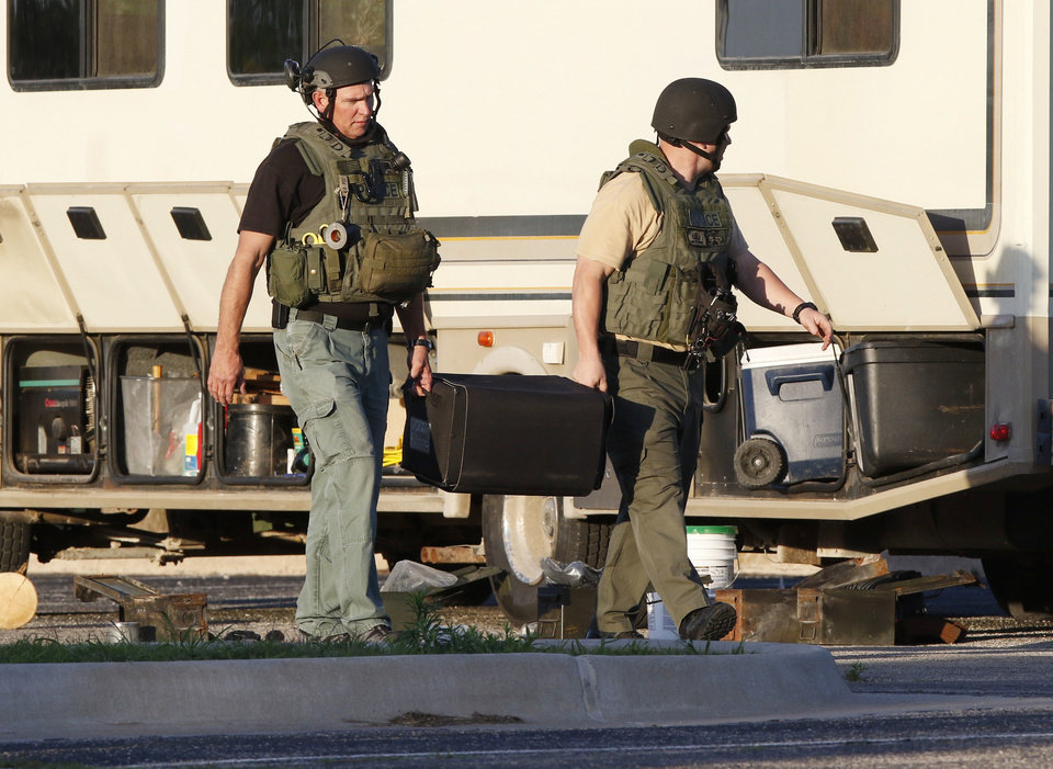 Photo -  Oklahoma City Police Department bomb squad members pick up a number of suspicious devices around an RV parked in Wheeler Park in Oklahoma City, including what appear to be hand grenades on May 26. [Photo by Paul Hellstern, The Oklahoman]