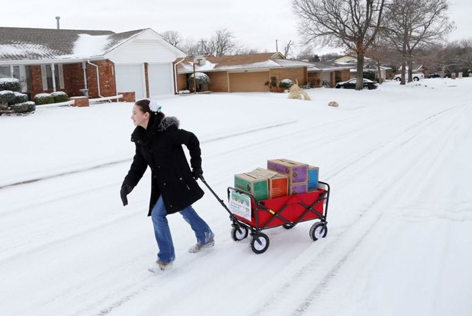 Photo - Girl Scout Katie Francis pulls her wagon full of boxes of cookies in 2014 in the snow through a neighborhood in Warr Acres selling cookies. Katie broke the record for the most Girl Scout cookies sold in a single season in 2014 and now has broken the record for the most cookies sold in the course of a Girl Scout's career. Photo by Doug Hoke, The Oklahoman Archives]