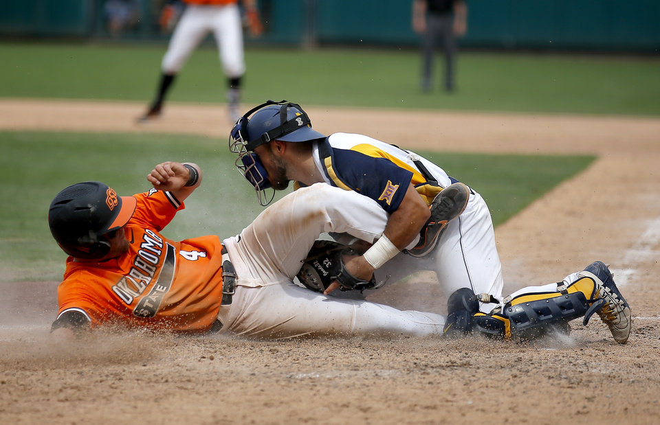 Photo - OSU's Andrew Navigato slides into home plate as West Virginia's Ivan Gonzalez tries to place the tag during the Big 12 baseball tournament game between Oklahoma State and West Virginia at the Chickasaw Bricktown Ballpark in Oklahoma City, Sunday, May 26, 2019.  [Sarah Phipps/The Oklahoman]