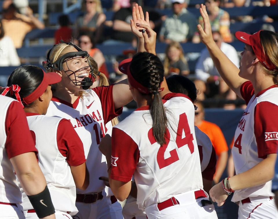 Photo - OU pitcher Paige Lowary (14), second from left, high fives teammates after the championship game of the Big 12 softball tournament between Oklahoma and Oklahoma State (OSU) at ASA Hall of Fame Stadium in Oklahoma City, Saturday, May 13, 2017. OU won 2-0. Photo by Nate Billings, The Oklahoman