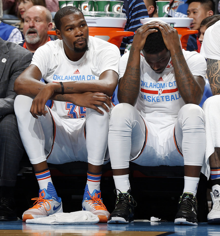 Photo - Oklahoma City's Kevin Durant (35), left, sits next to Anthony Morrow (2) after fouling out in overtime of an NBA basketball game between the Oklahoma City Thunder and the Golden State Warriors at Chesapeake Energy Arena in Oklahoma City, Saturday, Feb. 27, 2016. Golden State won 121-118 in overtime. Photo by Nate Billings, The Oklahoman
