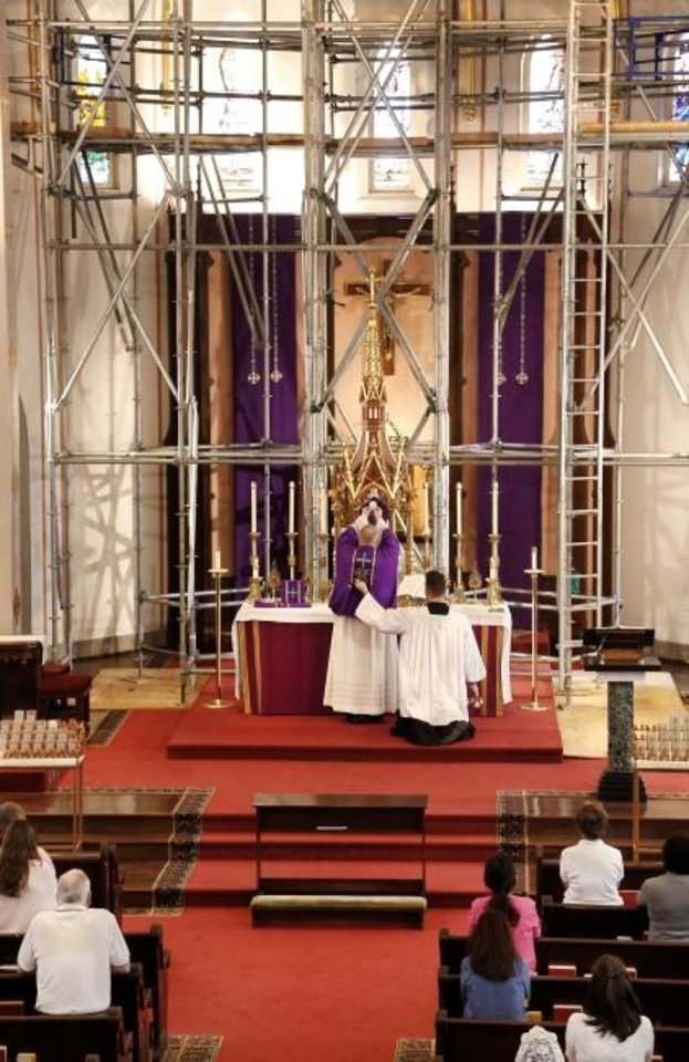 Photo -  The Rev. Price Oswalt celebrates Mass with worshipers amid scaffolding is in the sanctuary as crews repair the interior of St. Joseph Old Cathedral in downtown Oklahoma City. [Jim Beckel/The Oklahoman]