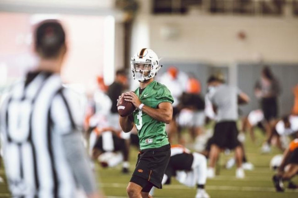 Photo -  Oklahoma State quarterback Spencer Sanders prepares to throw as condensation builds on the inside of his face shield during OSU's first practice of preseason camp Wednesday in Stillwater. [Bruce Waterfield/OSU Athletics]