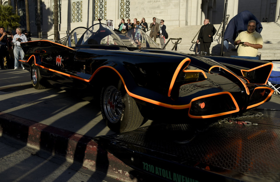 Photo - Fans gather around a Batmobile before a tribute to