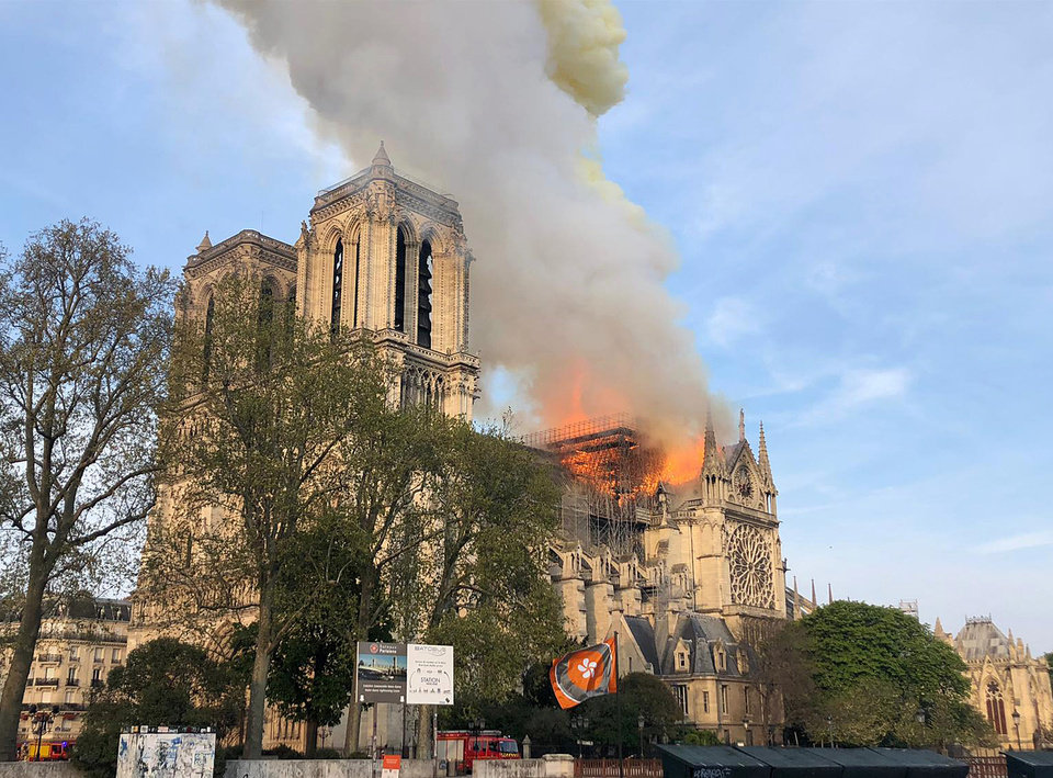 Photo - Notre Dame cathedral is burning in Paris, Monday, April 15, 2019. Massive plumes of yellow brown smoke is filling the air above Notre Dame Cathedral and ash is falling on tourists and others around the island that marks the center of Paris. (AP Photo)