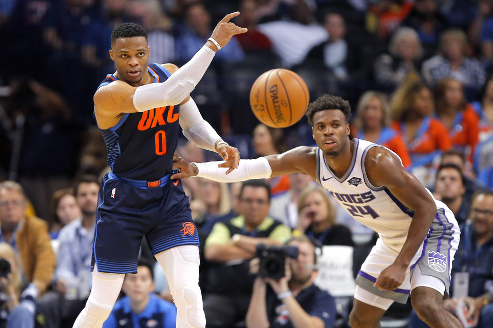 Photo - Oklahoma City's Russell Westbrook (0) passes the ball beside Sacramento's Buddy Hield (24) during an NBA basketball game between the Oklahoma City Thunder and the Sacramento Kings at Chesapeake Energy Arena in Oklahoma City, Sunday, Oct. 21, 2018. Photo by Bryan Terry, The Oklahoman