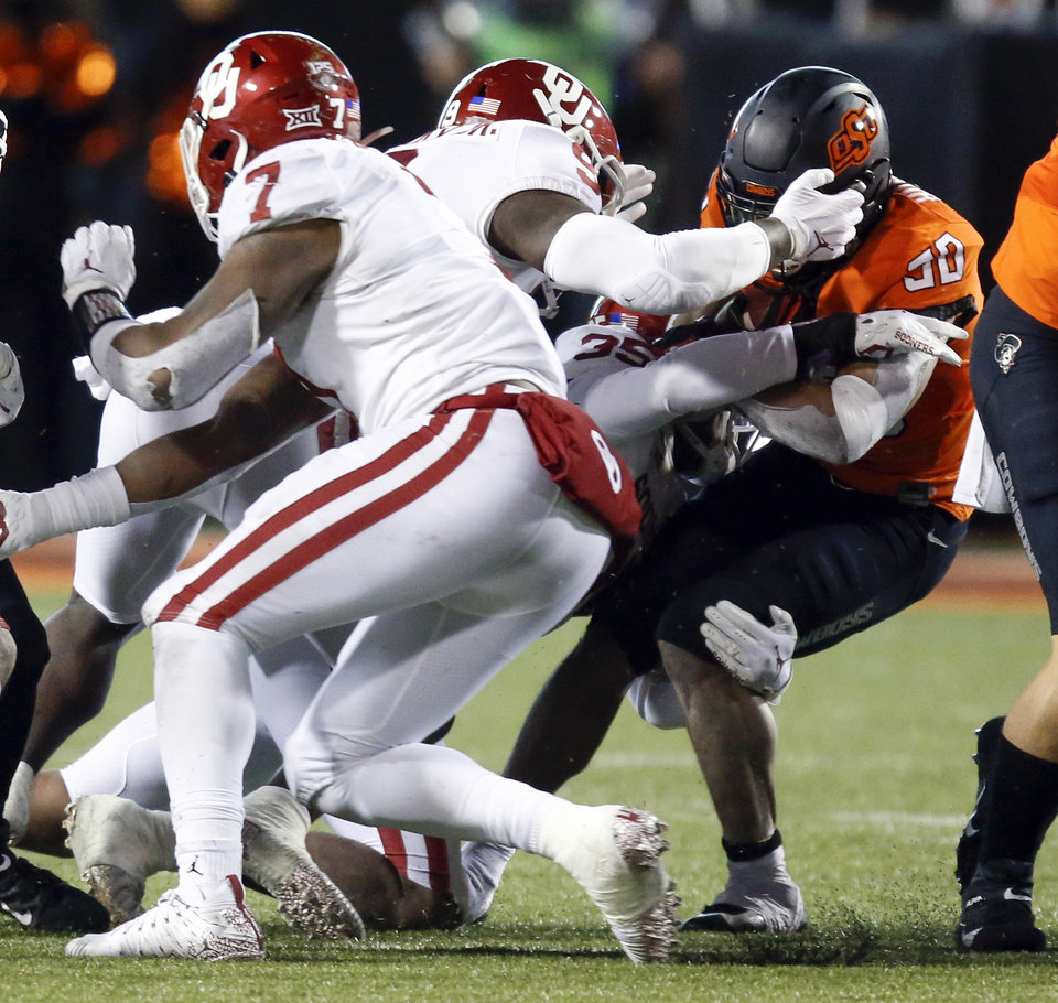 Photo - The OU defense stops Oklahoma State's Chuba Hubbard (30) as he carries the ball on fourth down and one in the fourth quarter during the Bedlam college football game between the Oklahoma State Cowboys (OSU) and Oklahoma Sooners (OU) at Boone Pickens Stadium in Stillwater, Okla., Saturday, Nov. 30, 2019. [Nate Billings/The Oklahoman]