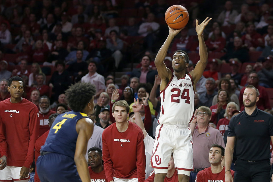 Photo - Oklahoma's Jamal Bieniemy (24) shoots a 3-pointer over West Virginia's Miles McBride (4) during an NCAA mens college basketball game between the University of Oklahoma Sooners (OU) and the West Virginia Mountaineers at the Lloyd Noble Center in Norman, Okla.,Saturday, Feb. 8, 2020. Oklahoma won 69-59. [Bryan Terry/The Oklahoman]