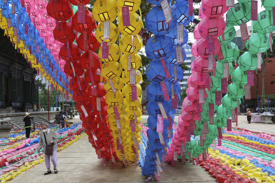 Photo -  A woman wearing a face mask to help curb the spread of the coronavirus passes by lantern decorations for Buddha's birthday at the Chogyesa temple in Seoul, Monday, June 29, 2020. This year a ceremony to celebrate the birthday was put off from April 30 to May 30 due to the coronavirus. (AP Photo/Ahn Young-joon)