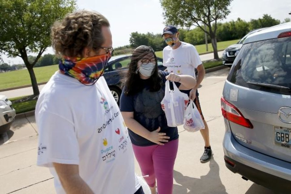 Photo -  Camp Chaverim Leadership In Training Assistant Directors Brian Stockton, left, and Jeff Gross, far right, meet Leadership in Training camper Gracia Mejia-Jacobson, 11, as she drops off baby items outside the Jewish Federation of Greater Oklahoma City during the camp's drive-thru baby shower. [Bryan Terry/The Oklahoman]