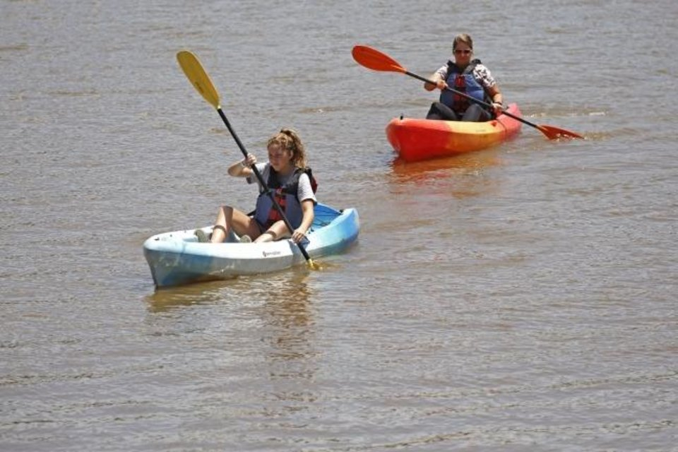 Photo -  People kayak down the river on June 23 at Riversport Adventures in Oklahoma City. [Paxson Haws/The Oklahoman]
