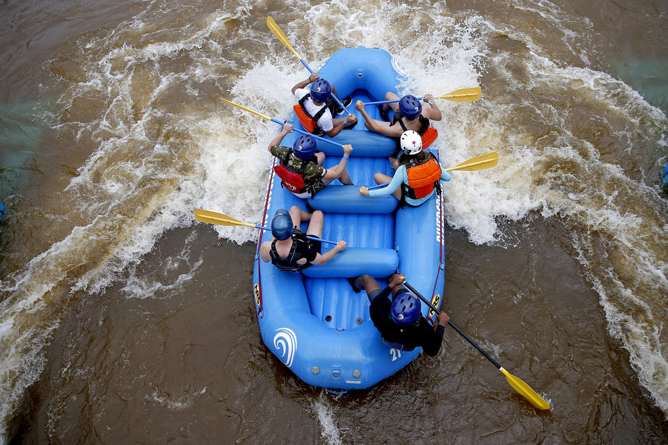 Photo -  A group of rafters make their way along the whitewater rafting course at Riversport Adventures in downtown Oklahoma City's Boathouse District on Tuesday. Riversport Adventures, which offers whitewater rafting, tubing and kayaking along with the Sky Trail ropes course, high speed slides and youth zone, re-opened on Saturday.  [Bryan Terry/The Oklahoman]