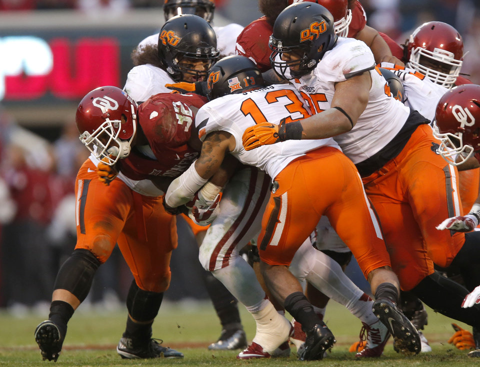 Photo - A host of Oklahoma State defenders tackle Oklahoma's Samaje Perine (32) during the Bedlam college football game between the University of Oklahoma Sooners (OU) and the Oklahoma State Cowboys (OSU) at Gaylord Family-Oklahoma Memorial Stadium in Norman, Okla., Saturday, Dec. 6, 2014. Photo by Sarah Phipps, The Oklahoman