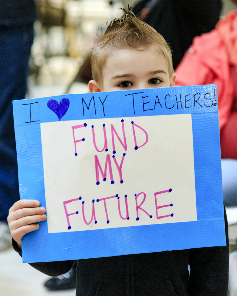 Photo - Five-year-old Nicholas Ambruso, of Edmond, holds a sign to support teachers during the ninth day of a walkout by Oklahoma teachers at the state Capitol in Oklahoma City, Okla. on Tuesday, April 10, 2018.   Photo by Chris Landsberger, The Oklahoman