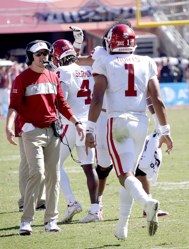 Photo - Oklahoma head coach Lincoln Riley waits to congratulate Jalen Hurts (1) on a touchdown in the fourth quarter during the Red River Showdown college football game between the University of Oklahoma Sooners (OU) and the Texas Longhorns (UT) at Cotton Bowl Stadium in Dallas, Saturday, Oct. 12, 2019. OU won 34-27. [Sarah Phipps/The Oklahoman]