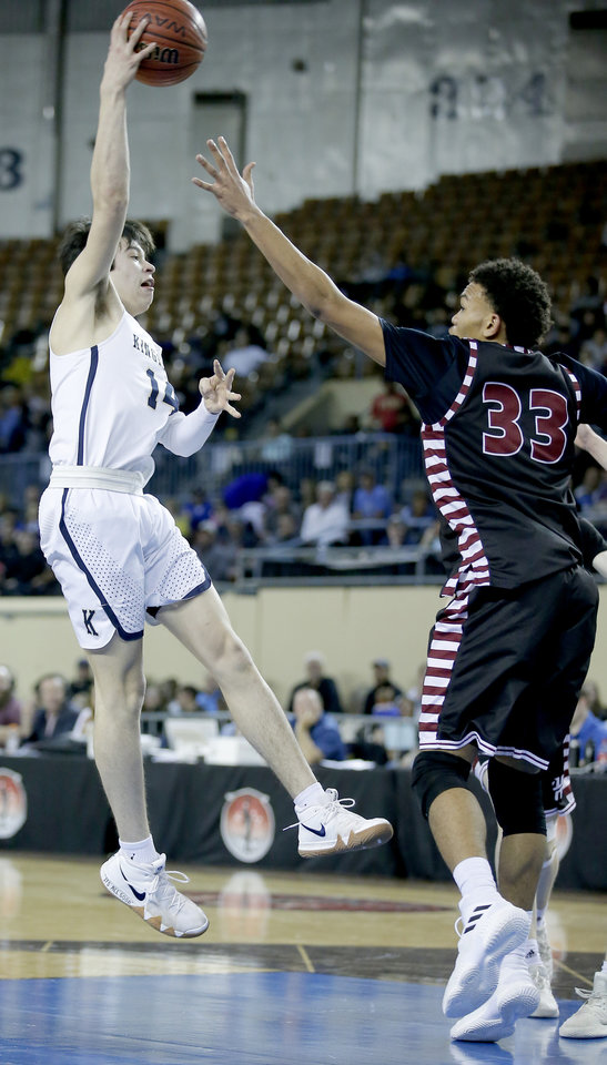 Photo - Kingfisher's Bijan Cortes passes as Holland Hall's Brock Davis defends during a 4A boys semifinal game last season. Cortes scored 21 points against Tuttle on Tuesday. [Sarah Phipps, The Oklahoman]