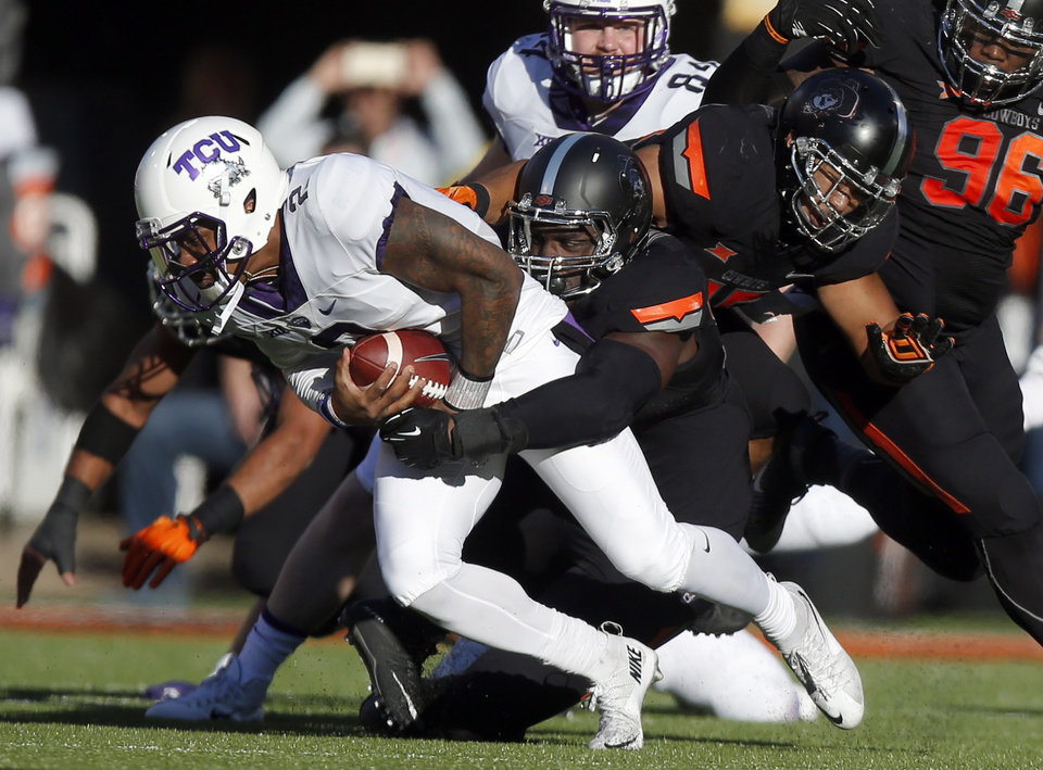 Photo - Oklahoma State's Jarrell Owens (93) brings down TCU's Trevone Boykin (2) during the college football game between the Oklahoma State Cowboys (OSU) and TCU Horned Frogs at Boone Pickens Stadium in Stillwater, Okla., Saturday, Nov. 7, 2015. Photo by Sarah Phipps, The Oklahoman