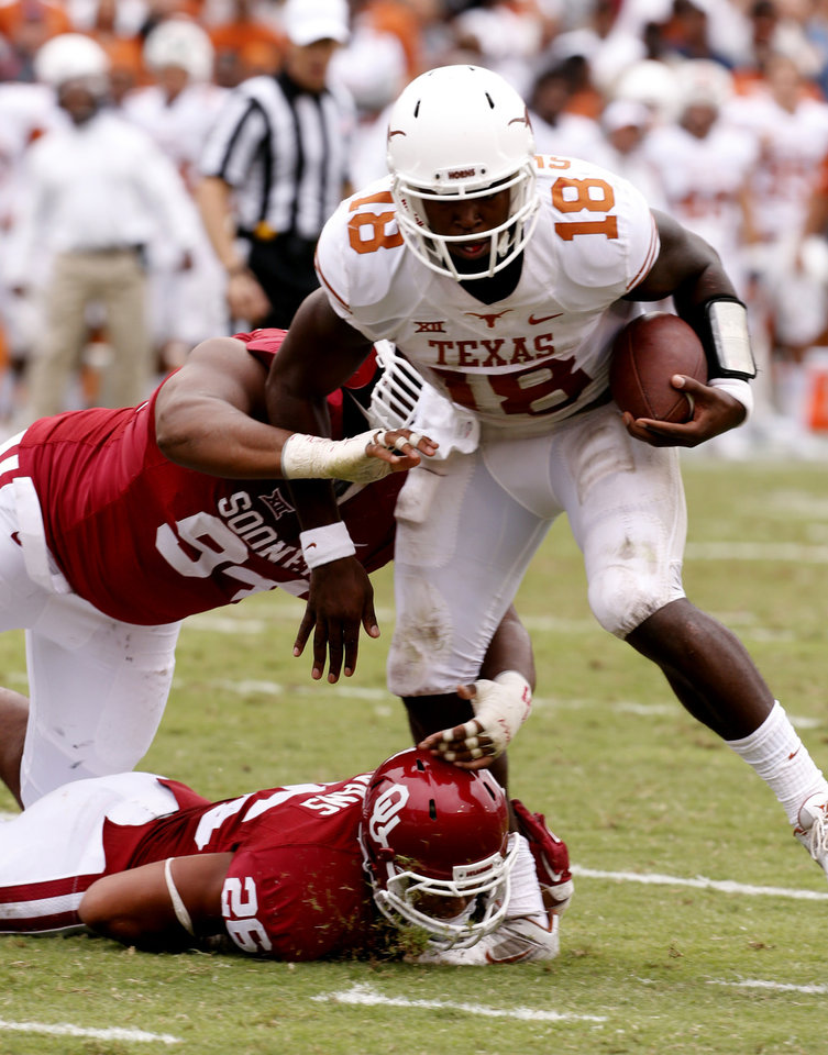 Photo - Oklahoma's Torrea Peterson (94) and Jordan Evans (26) stopTexas' quarterback Tyrone Swoopes (18) on a two point conversion try during the second half of the Red River Showdown college football game between the University of Oklahoma Sooners (OU) and the University of Texas Longhorns (UT) at the Cotton Bowl in Dallas, Texas on Saturday, Oct. 11, 2014. 