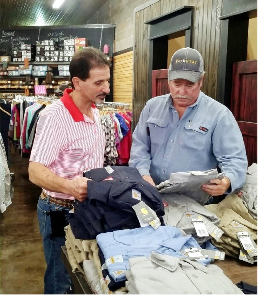Photo -  Store owner Craig Mettry, left, discusses fire-resistant work clothing with customer Terry Foster. [Photo provided]