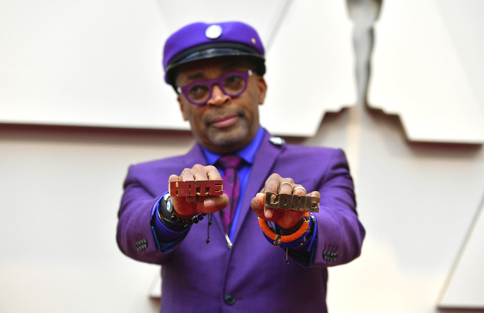 Photo -  Spike Lee holds up brass knuckles reading