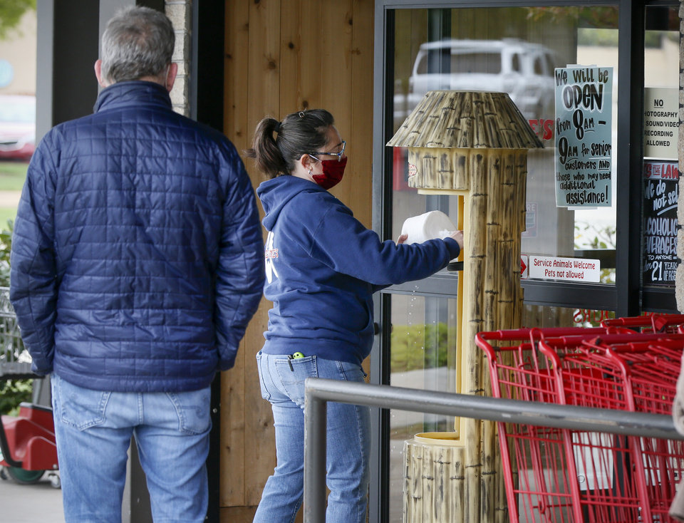 Photo - An employee refills a dispenser of wipes as a customer waits to enter Trader Joe's in Nichols Hills, Okla., Monday, April 13, 2020. [Nate Billings/The Oklahoman]