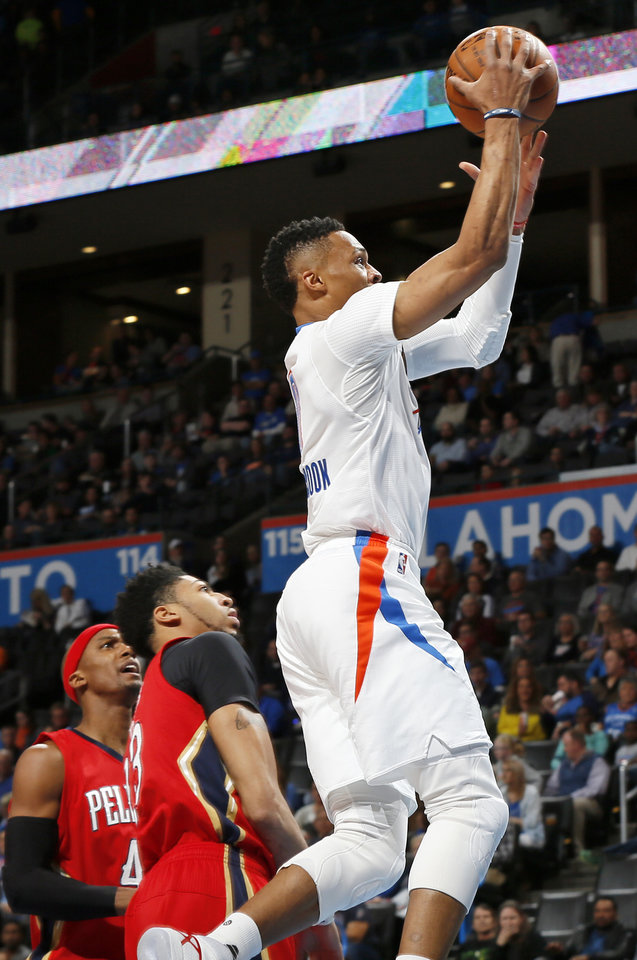 Photo - Oklahoma City's Russell Westbrook (0) takes the ball past New Orleans' Dante Cunningham (44), left, and Anthony Davis (23) during an NBA basketball game between the New Orleans Pelicans and the Oklahoma City Thunder at Chesapeake Energy Arena in Oklahoma City, Thursday, Feb. 11, 2016.  Photo by Nate Billings, The Oklahoman