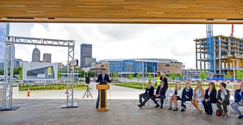 Photo -  The Love family listens as Mayor David Holt reflects on their donation of $2 million to the Scissortail Park Foundation. The changing downtown skyline, including several floors of the future Omni  Hotel, can be seen in the background of what will be the Love's Travel Stops Stage and Great Lawn. [Chris Landsberger/The Oklahoman]