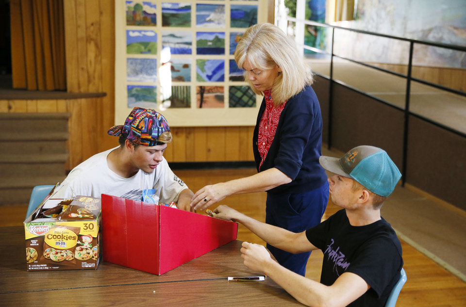 Photo - Principal Elizabeth Ressel talks to Kenneth Curry, 16, of Comanche, left, and Bruce Butler, 17, of Comanche, as she hands out snacks during break time at FAME Academy, an alternative school in Comanche Public Schools, in Meridian, Okla., Wednesday, Oct. 3, 2018. Photo by Nate Billings, The Oklahoman