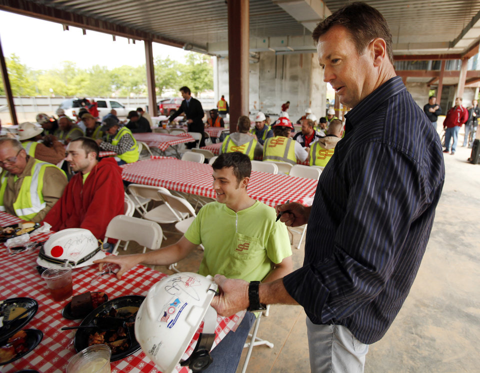 Photo - DORMS: Head football coach Bob Stoops autographs hard hats for workers treated to a free lunch during the official