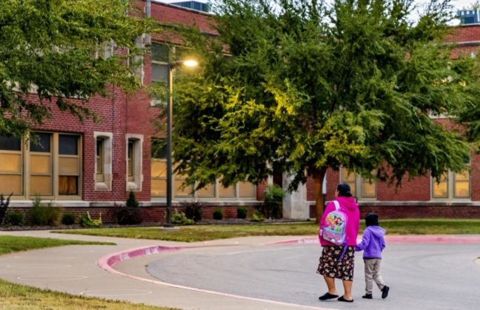 Photo -  A woman walks with her child Tuesday as Pre-K and kindergarten arrive for the first day of in person class.   [Chris Landsberger/The Oklahoman]