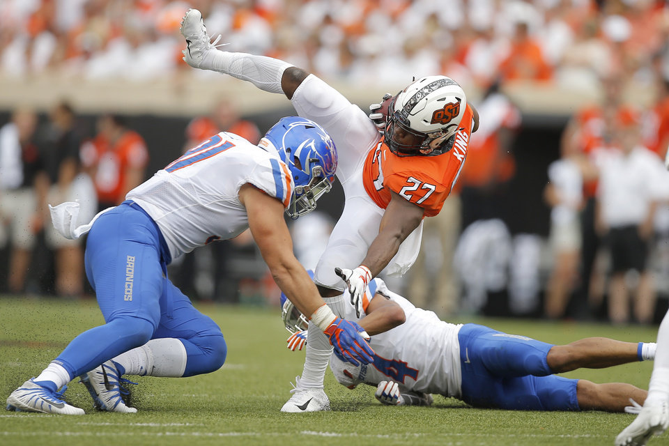 Photo - Oklahoma State's J.D. King (27) keeps his balance between Boise State's Durrant Miles (91) and DeAndre Pierce (4) during a college football game between the Oklahoma State University Cowboys (OSU) and the Boise State Broncos at Boone Pickens Stadium in Stillwater, Okla., Saturday, Sept. 15, 2018. Oklahoma State won 44-21. Photo by Bryan Terry, The Oklahoman