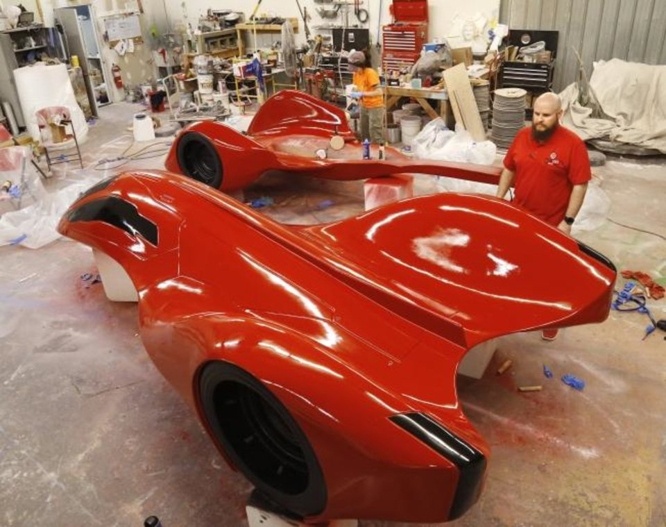 Photo -  Jason Taylor, front, looks at the concept car for this year's auto show as Amanda Robles polishes the part of the car that will be the lower half and the front wheels on the car.  Taylor is vice-president of Taylor Foam, and Robles is an artist with the company.