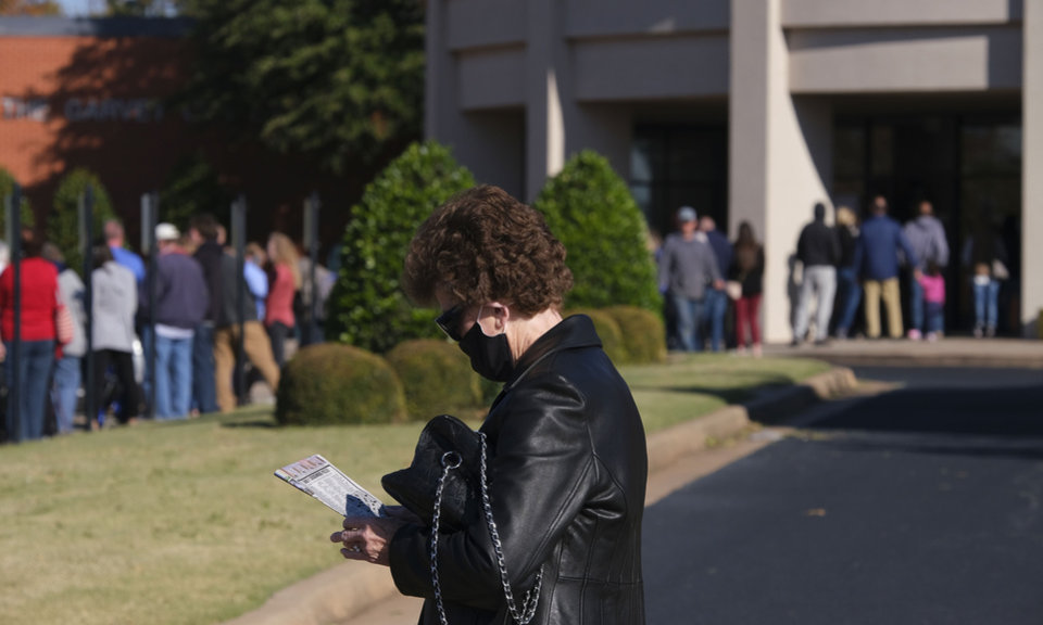 Photo - A woman works a crossword puzzle while in line. Election Day voting at Oklahoma Christian University in Edmond, Tuesday, November 3, 2020. [Doug Hoke/The Oklahoman]