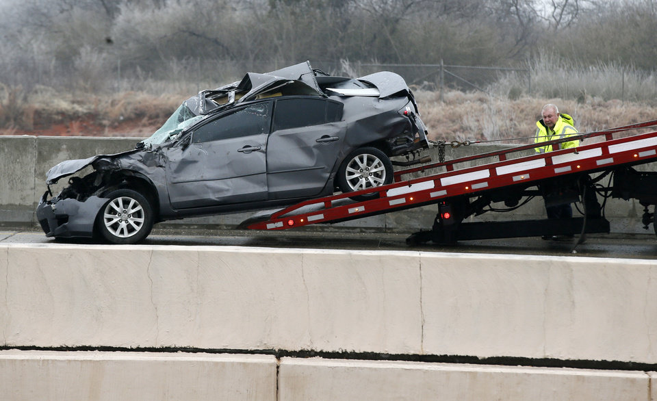 Photo - A wrecker removes a car involved in an accident on the entrance ramp to westbound I-44 near NW 63rd and I-235 during freezing rain in Oklahoma City, Wednesday, Feb. 27, 2019. by Nate Billings, The Oklahoman