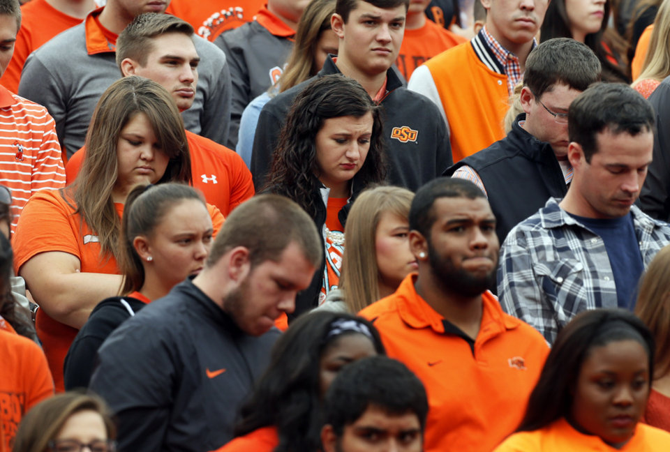 Photo - OSU fans observe a moment of silence for those killed and injured when a car crashed into spectators at the homecoming parade before a college football game between the Oklahoma State University Cowboys (OSU) and the Kansas Jayhawks (KU) in Stillwater, Okla., Saturday, Oct. 24, 2015. Photo by Nate Billings, The Oklahoman