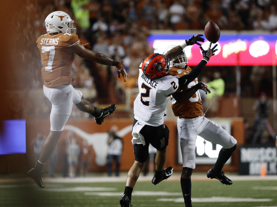 Photo - Texas linebacker Caleb Johnson (30) breaks up a pass intended for Oklahoma State wide receiver Tylan Wallace (2) during the second half of an NCAA college football game Saturday, Sept. 21, 2019, in Austin, Texas. (AP Photo/Eric Gay)