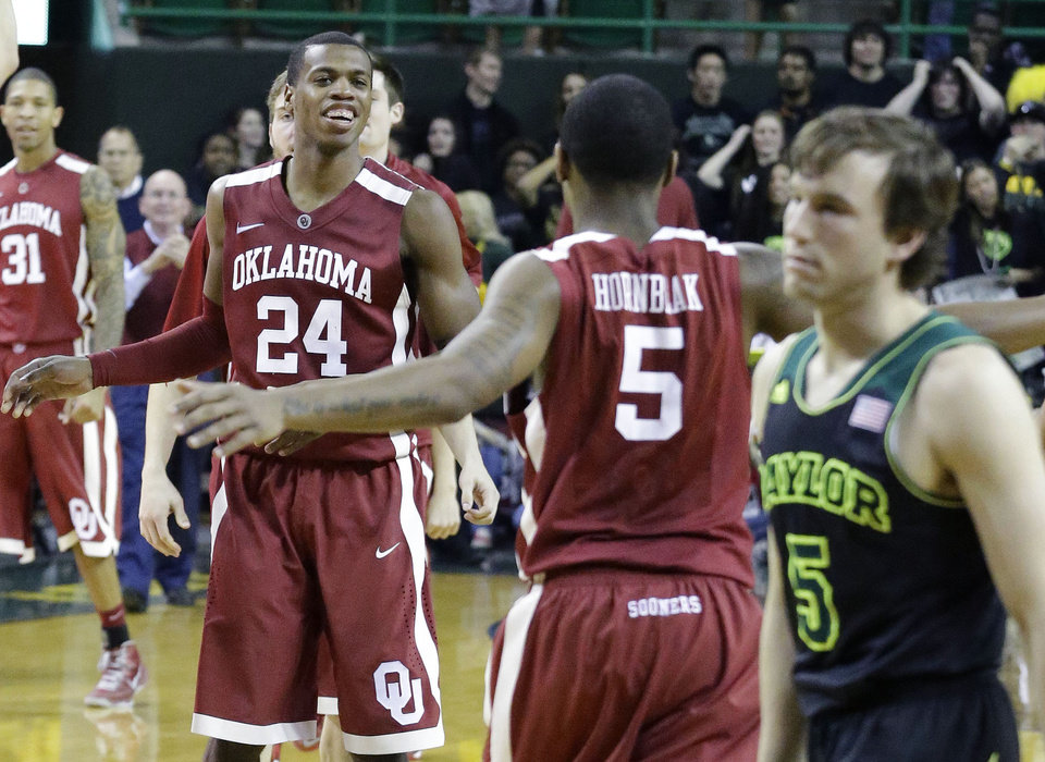 Photo - Oklahoma guard Je'lon Hornbeak (5) heads over to celebrate with teammate Buddy Hield (24) as Baylor guard Brady Heslip (5) walks off the court after an NCAA college basketball game Saturday, Jan. 18, 2014, in Waco, Texas. Oklahoma won 66-64. (AP Photo/LM Otero)