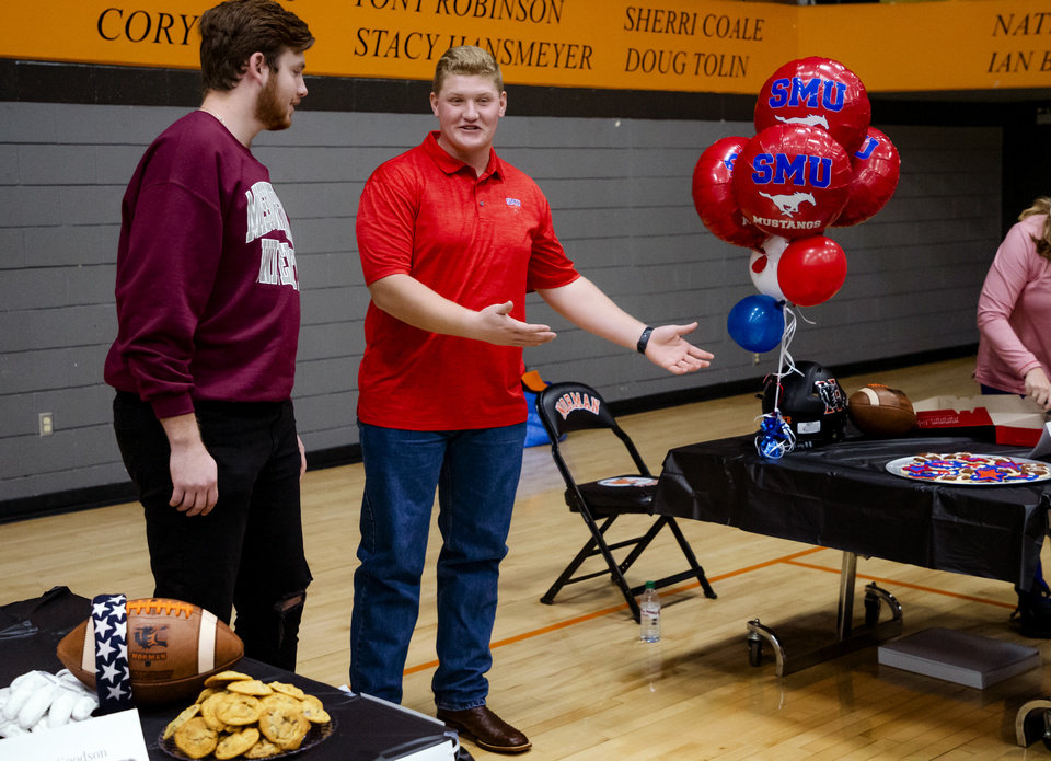 Photo - Missouri State University signee, Grant Goodson, left, and Southern Methodist University signee Ben Sparks celebrate signing their letter of intent with classmates during a national signing day ceremony for football at Norman High School in Norman Okla. on Wednesday, Dec. 18, 2019.   [Chris Landsberger/The Oklahoman]
