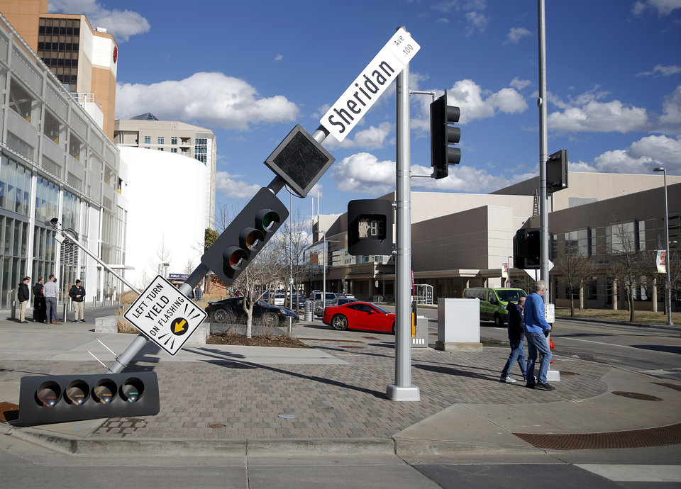 Photo - Pedestrians waited to cross the street after high winds blew down the signal at Sheridan and Robinson avenues in downtown Oklahoma City on Wednesday. [Photo by Sarah Phipps, The Oklahoman]