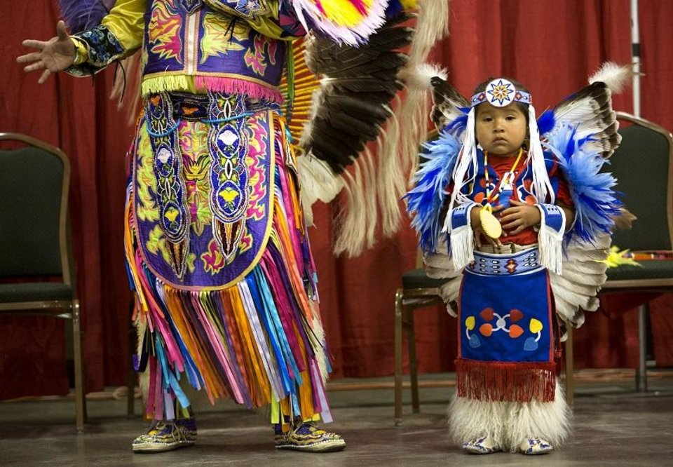 Photo - Cecil Gray II, left, explains the significance of various Native American dances at the Red Earth Festival in the Cox Convention Center in Oklahoma City, Friday, June 8, 2018. Next to him is his son, Cecil Gray III. Photo by Anya Magnuson, The Oklahoman